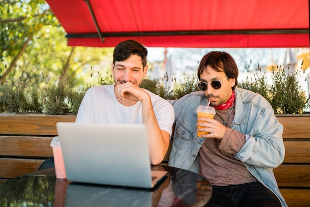 Two young friends using laptop at coffee shop.