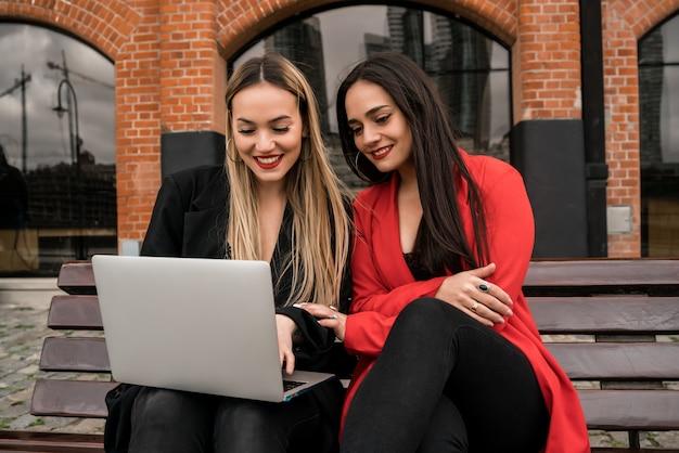 Due giovani amici che per mezzo di un computer portatile all'aperto.