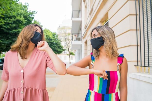 屋外に立っている間、フェイスマスクを着用し、肘をぶつけて挨拶する2人の若い友人