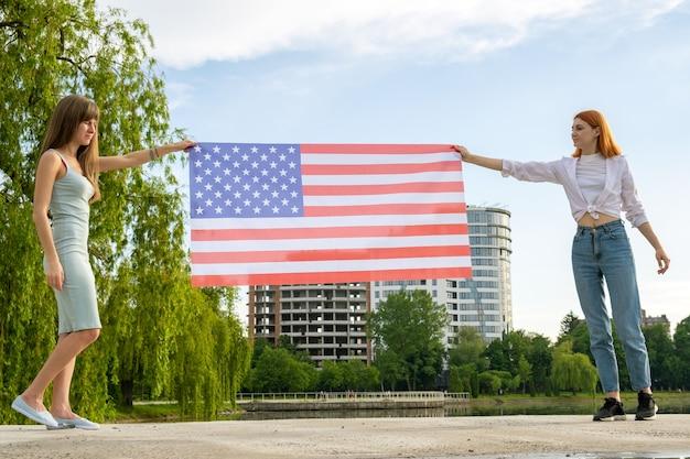 Две молодые друзья женщины держат в руках национальный флаг сша на закате.