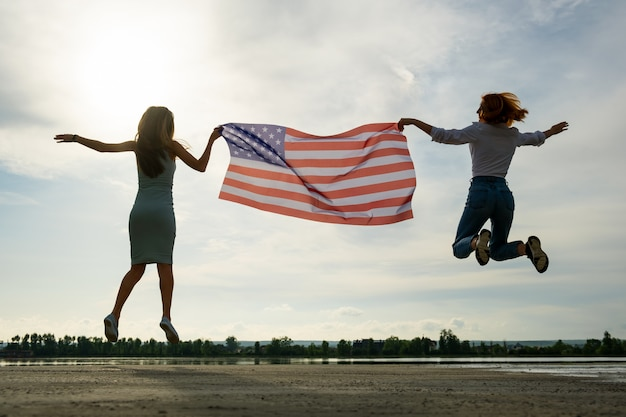 2 молодых друз женщины держа национальный флаг сша скача вверх совместно outdoors на заходе солнца. силуэт девушки, празднование дня независимости соединенных штатов.