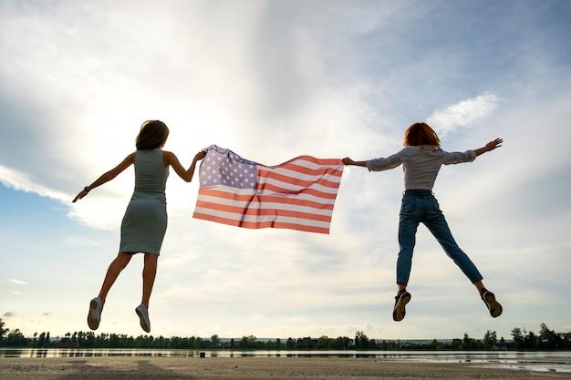 Две молодые женщины друзей с национальным флагом сша, подпрыгивая вместе на открытом воздухе на берегу озера.