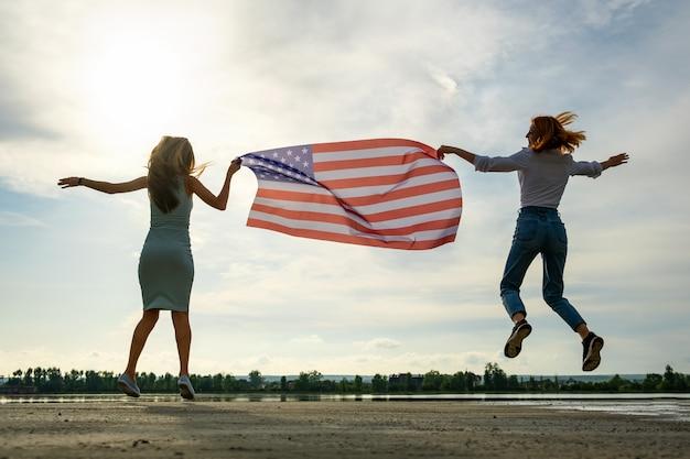 Две молодые друзья женщины с национальным флагом сша