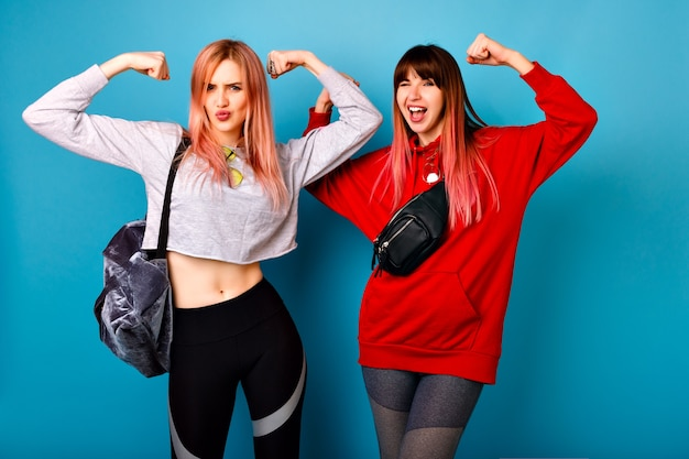 Two young funny pretty hipster women wearing sportive bright casual outfits, showing biceps and making grimaces, going crazy together,  blue wall