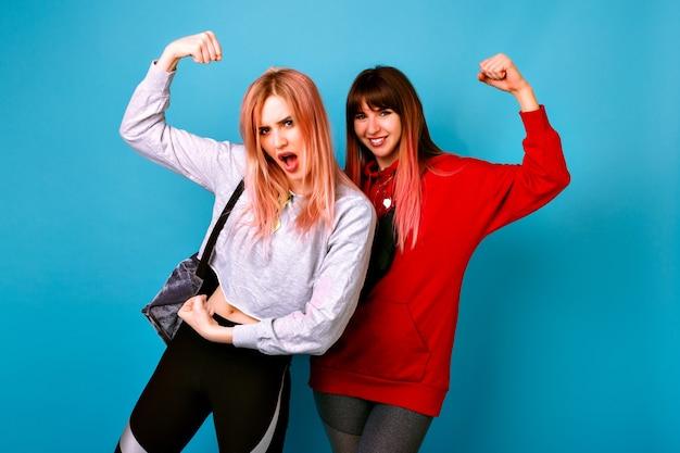 Due giovani donne divertenti piuttosto hipster che indossano abiti casual luminosi sportivi, mostrando bicipiti e facendo smorfie, impazzendo insieme, muro blu