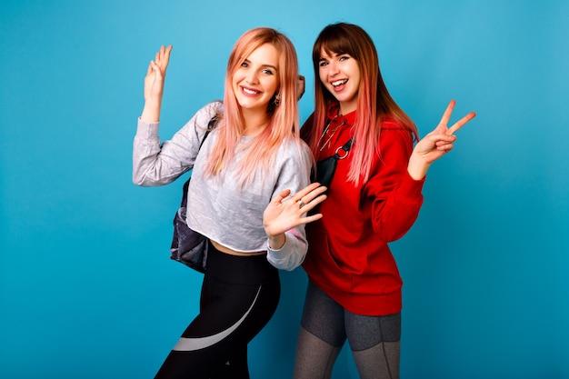 スポーツの明るいカジュアルな服を着て、笑顔で叫んで、あなたに挨拶する2人の若い面白いかわいいヒップスターの女性、青い壁