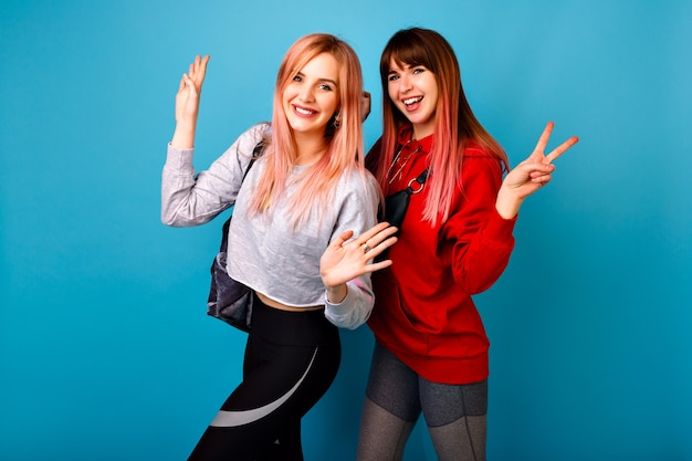Due giovani donne divertenti piuttosto hipster che indossano abiti casual luminosi sportivi, sorridendo urlando e salutando te, muro blu