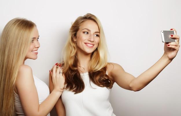 携帯電話で自分撮りをしている 2 人の面白い若い女性