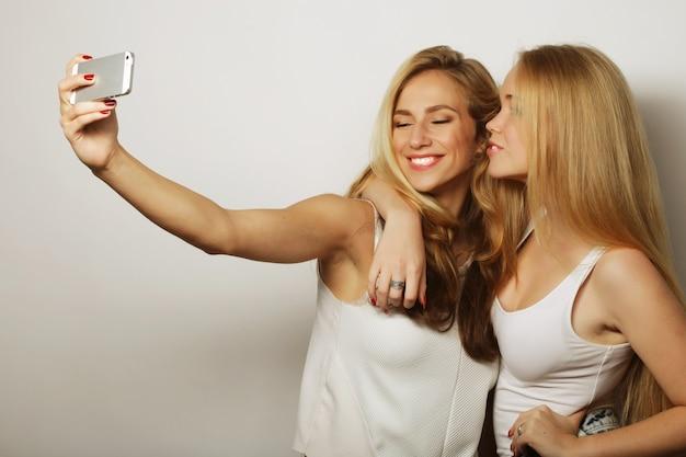 Две молодые смешные женщины, делающие селфи с мобильным телефоном