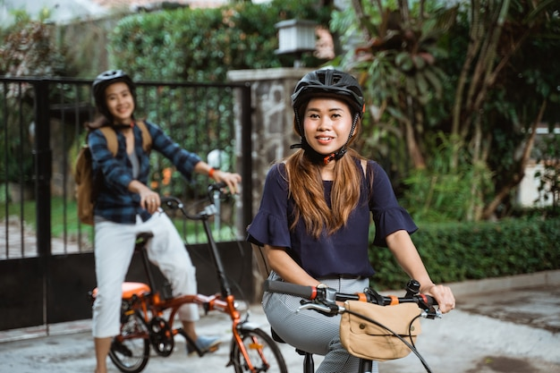 Two young girl are ready go to school by folding bicycle