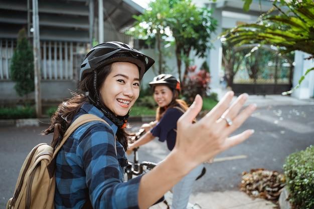 2人の少女が準備ができて学校に行く手ジェスチャーを誘う