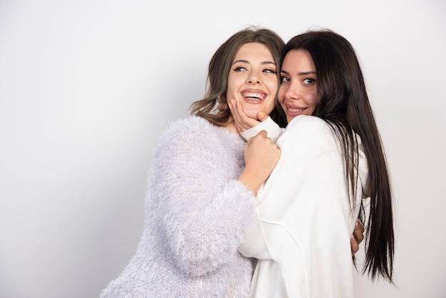 Две молодые девушки весело и улыбается на белой стене.
