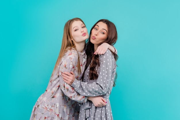 Two young girl friends hugging and kissing isolated