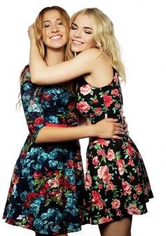 Две молодые девушки друзей стоя вместе и весело. изолированные на белом.