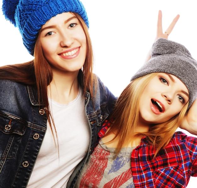 一緒に立って楽しんでいる2人の若いガールフレンド。白で隔離。