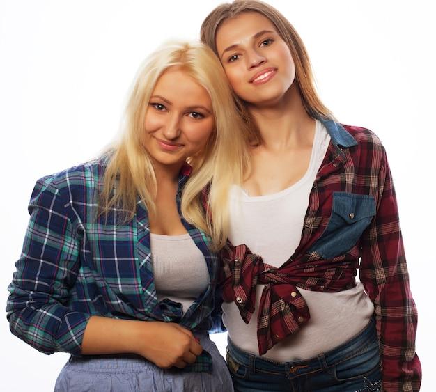 一緒に立って楽しんでいる2人の若いガールフレンド。カメラを見てください。