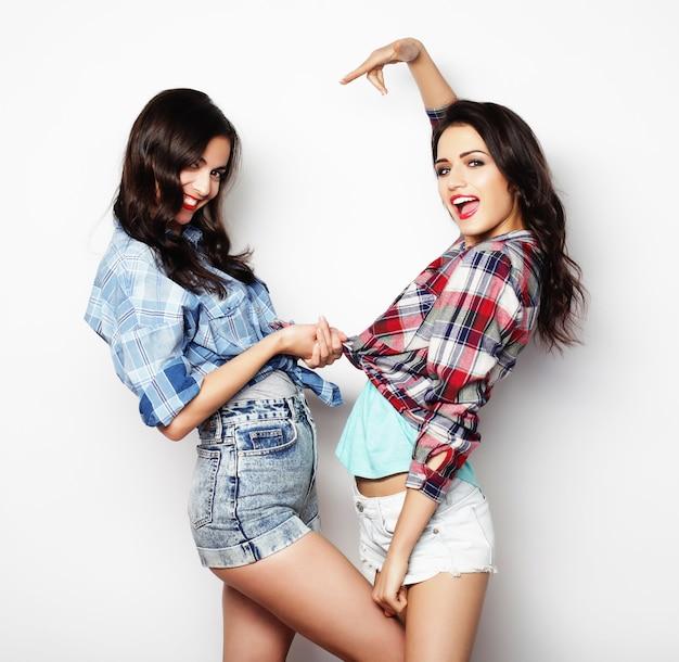 Две молодые девушки друзья стояли вместе и веселились.