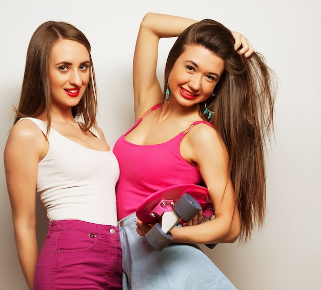 Two young girl friends standing together and looking at camera. over grey background.