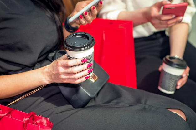 Two young girl friends use smartphones on hand and drinking coffee, sitting in the coffee cafe.