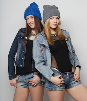 Two young girl hipster friends standing together