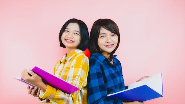 2つの若い女の子笑顔とノートを保持
