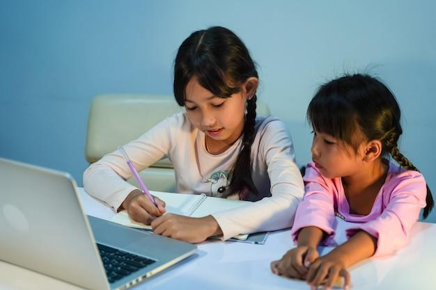 두 명의 어린 소녀가 전염병 검역 개념인 코로나바이러스(covid-19) 발병 기간 동안 집에서 노트북을 사용하여 온라인으로 공부합니다.