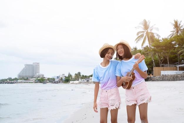 帽子ピンクのジーンズと青いシャツを着て2つの若い女の子が美しいビーチでウクレレを演奏