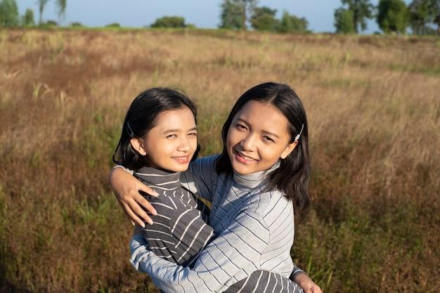 Две молодые девушки с голубым небом счастливая молодая девушка
