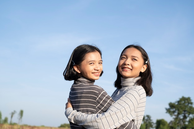 Two young girl with blue sky happy young girl