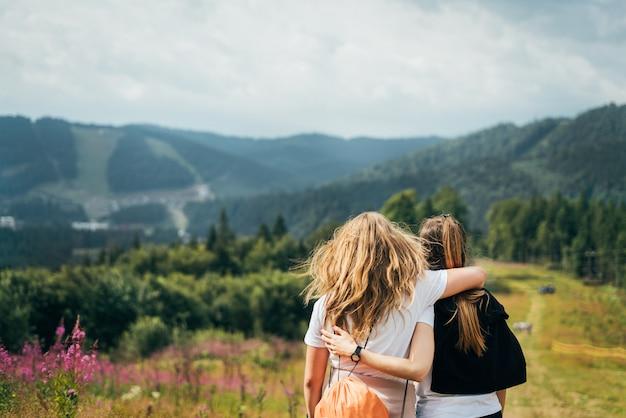 Две молодые подружки стоят на горе, обнимаются и наслаждаются природой с рюкзаком на цветущих склонах в теплый солнечный день. дружба и жажда развлечений и единения с природой