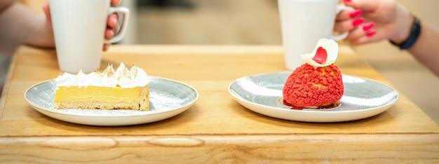 야외 카페에서 테이블에 앉아 케이크 조각으로 커피를 마시는 두 젊은 여자 친구