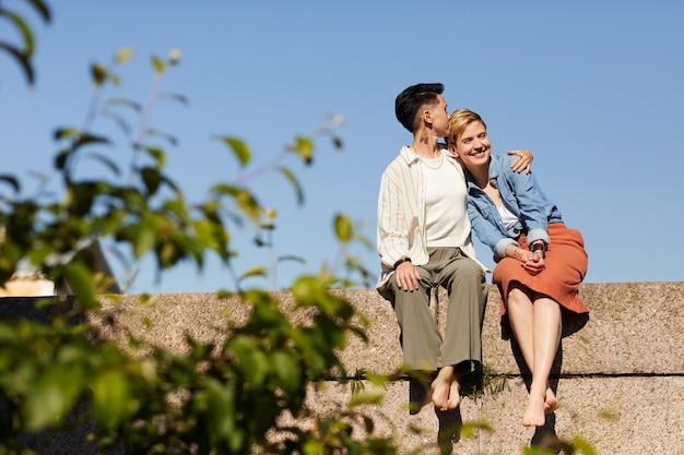 屋外に座って抱き合って楽しんでいる2人の若いガールフレンド