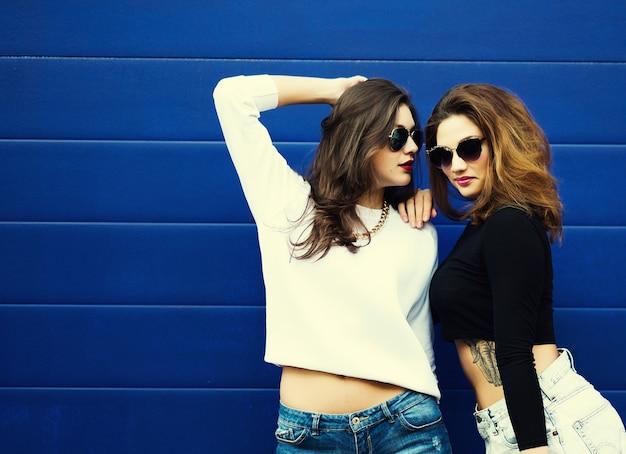 Две молодые подруги в солнцезащитных очках с удовольствием. образ жизни. Premium Фотографии