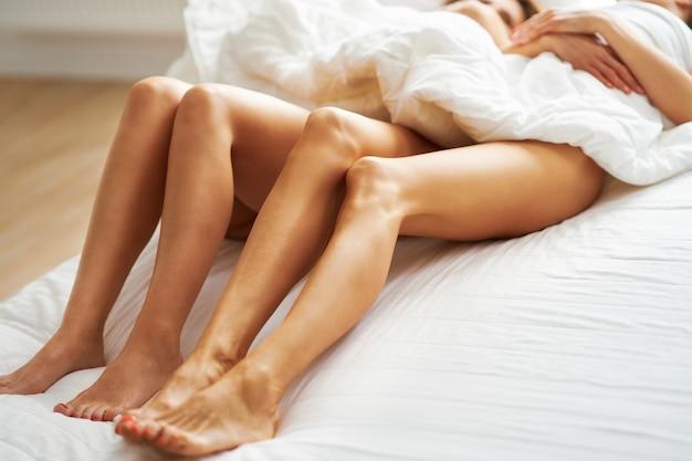 ベッドの上の2人の若いガールフレンド。高品質の写真