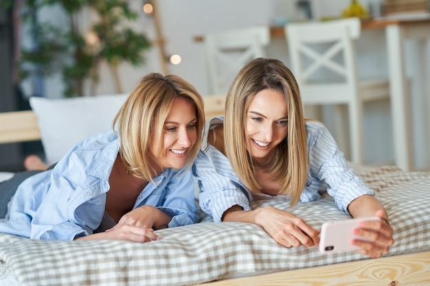 ベッドの上で自分撮りをしている2人の若いガールフレンド。高品質の写真