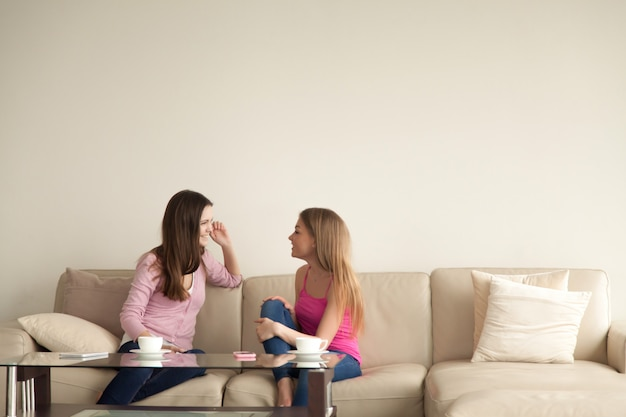 Two young girlfriends relaxing at home and having personal conversation