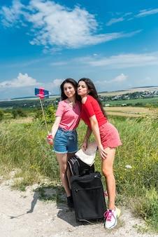 Две молодые подруги делают селфи на поле летом