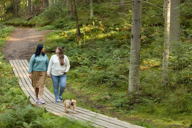 Two young girlfriends walking along the wooden path with their dog and talking in the forest