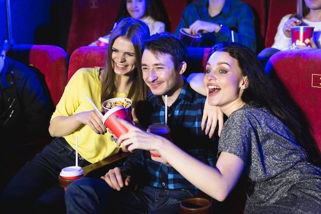 Две молодые девушки и парень смотрят комедию в кинотеатре. юные друзья смотрят кино в кинотеатре. группа людей в театре с попкорном и напитками