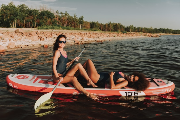 Two young girls are laying on surf in the water.