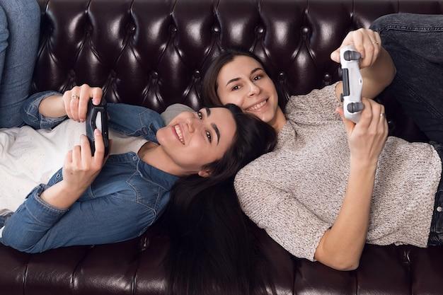 2人の若い女の子がゲーム機をプレイしていて、楽しい女性が家で休んでいます。高品質の写真