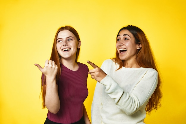 Two young girls are pointing fingers aside and laughing standing