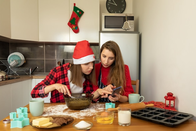 Two young girls are preparing christmas cookies at home in the kitchen. t
