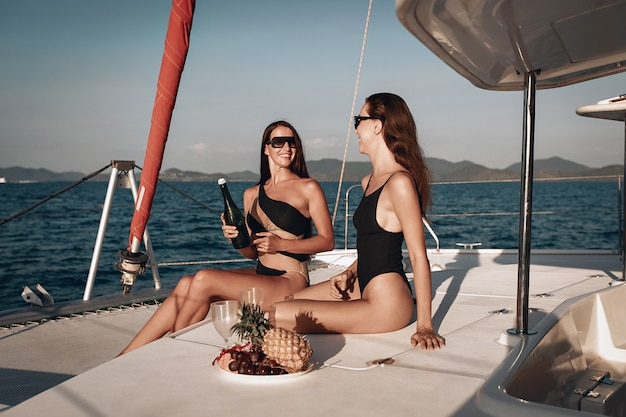 Two young girls in black bodysuit swimsuit and sunglasses are happily spending their summer holidays drinking champagne on the yacht