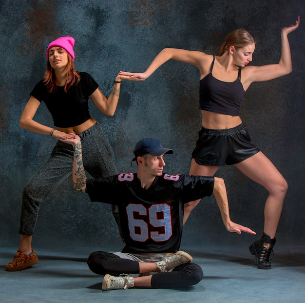 The two young girls and boy dancing hip hop at the blue