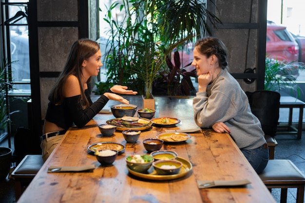 Two young girls chatting in an asian cafe