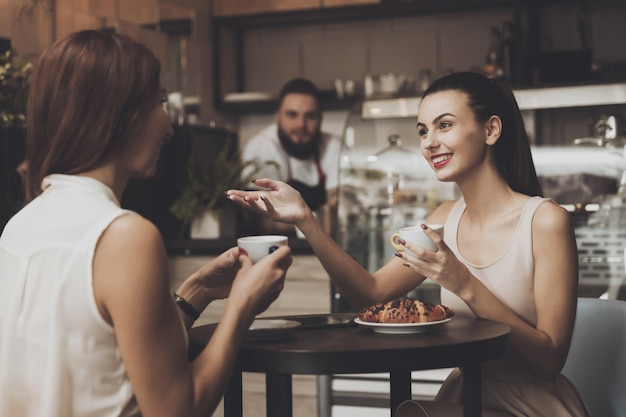 Two young girls communicate in a cafe at the table