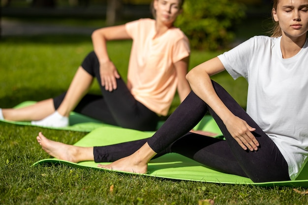 野外の公園で緑の芝生の上のヨガマットでストレッチをしている2人の若い女の子。