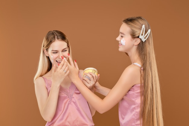 Two young girls foolishly applying face of each other with acne cream