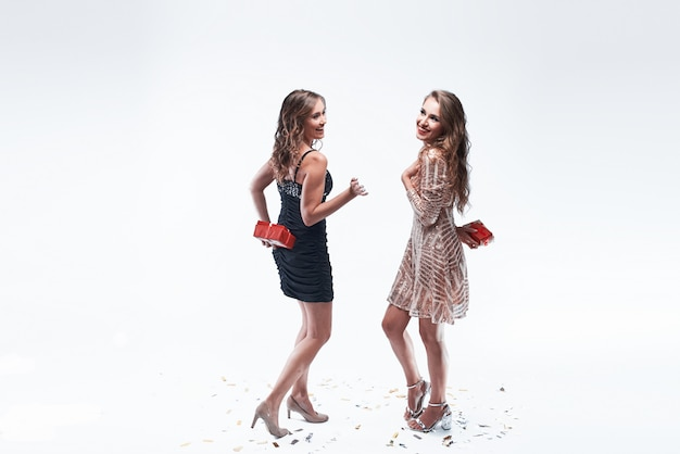 Two young girls friends holding gifts behind the back going to give them each other.